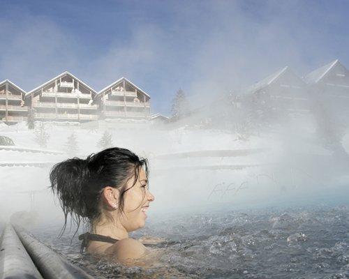 A woman enjoying in an outdoor hot tub.