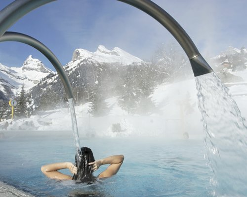 A woman having shower at the heated outdoor swimming pool alongside mountains during winter.
