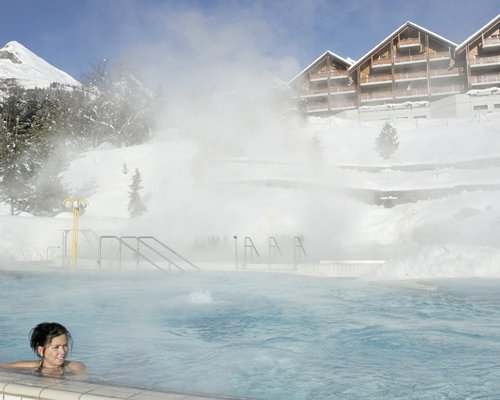 An outdoor large hot tub alongside the resort covered in snow.