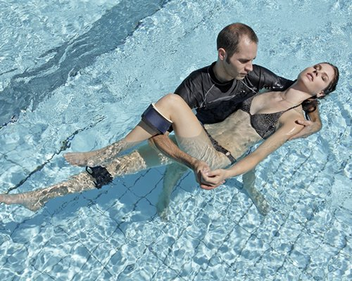 A couple swimming in an outdoor swimming pool.