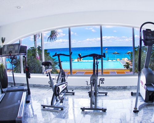 A well equipped indoor fitness center with a beach view.