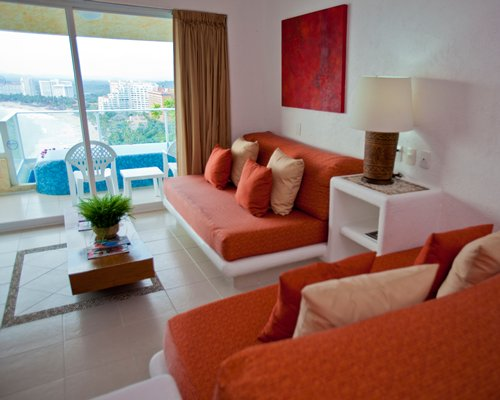 A well furnished living room with a balcony and beach view.