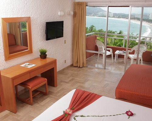 A well furnished bedroom with queen bed television balcony patio furniture and beach view.