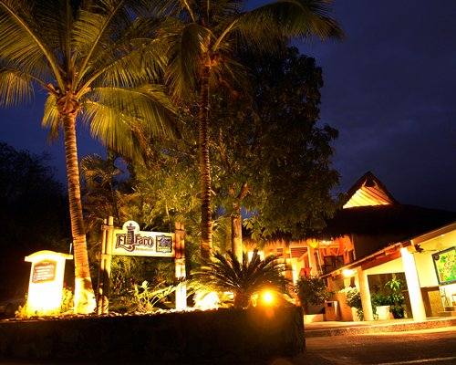 Entrance to Pacifica Sands with a signboard and palm trees at dusk.