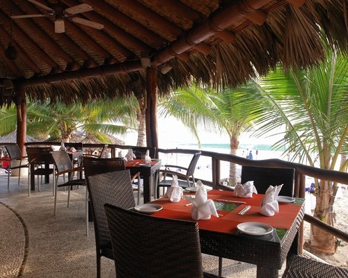 A well furnished restaurant area surrounded by trees and ocean view.