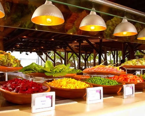 An indoor buffet area with various sliced vegetables.