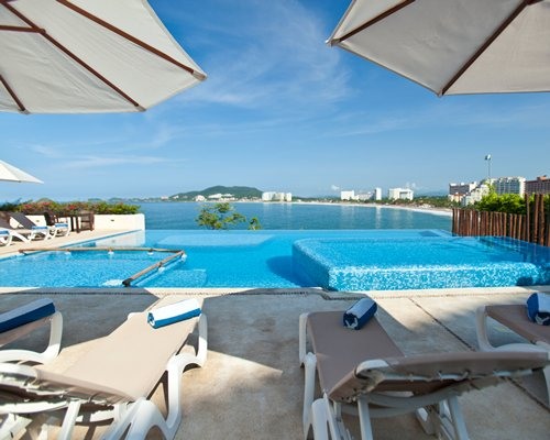 Large outdoor swimming pool with chaise lounge chairs and sunshades alongside the ocean.