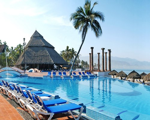 Outdoor swimming pool with chaise lounge chairs thatched sunshades and palm trees alongside the beach.