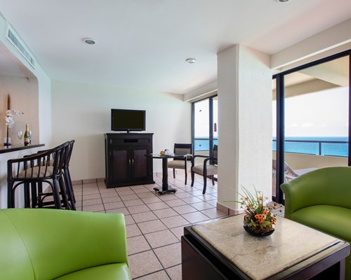 A well furnished living room with a television and balcony facing the ocean.