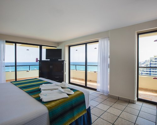 A well furnished bedroom with a television and a beach view.