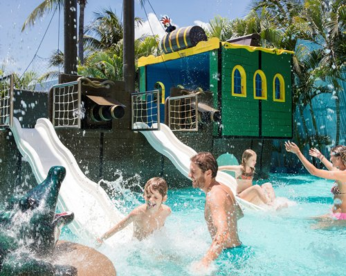 View of people playing at outdoor water theme park.