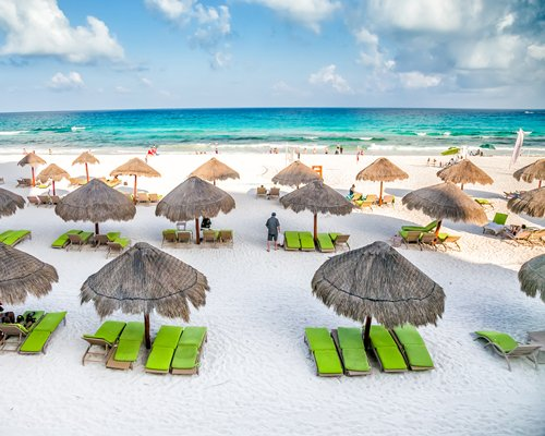 View of beach and ocean with chaise lounge chairs and thatched sunshades.