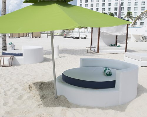 A view of the lounge chair with sunshades on a beach alongside a resort.