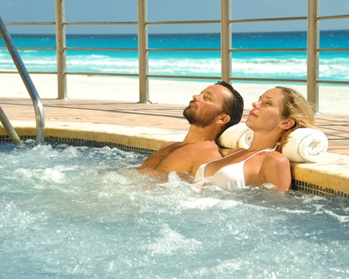 A couple relaxing in a hot tub alongside the ocean.