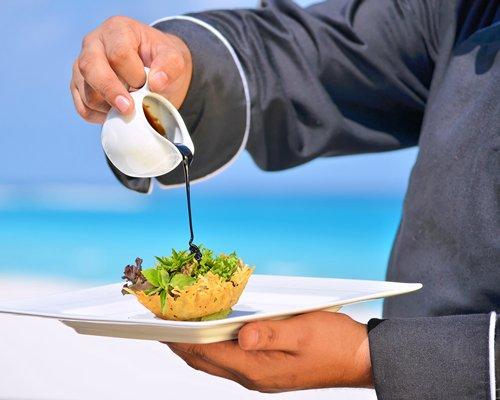 A man holding a food item alongside the beach.