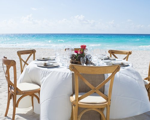 A view of the ocean from the beach with a dining table.