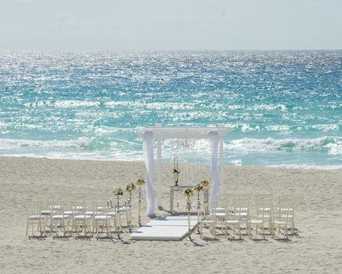 A scenic view of a beach wedding altar alongside the ocean.