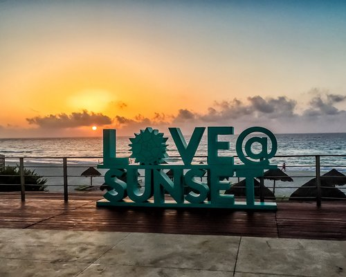 Sign board of Love @ Sunset at Sunset Royal Beach Resort with thatched sunshades alongside the beach.