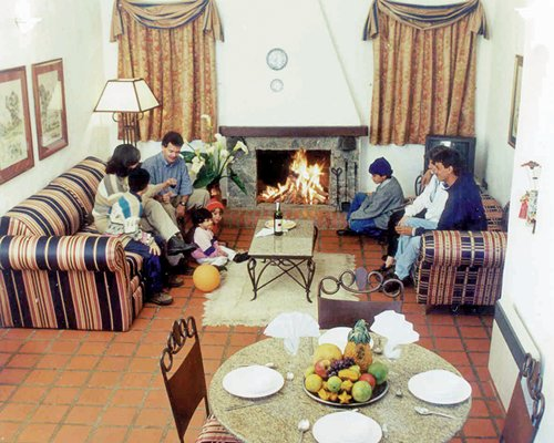 A family sitting in an open plan living and dining area with television and fire at the fireplace.