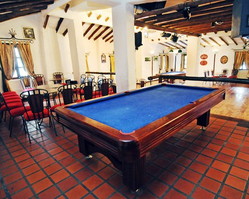 Indoor recreation room with a dining area and pool tables.