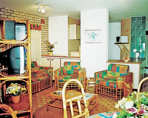 A well furnished living room with a television alongside a kitchen.