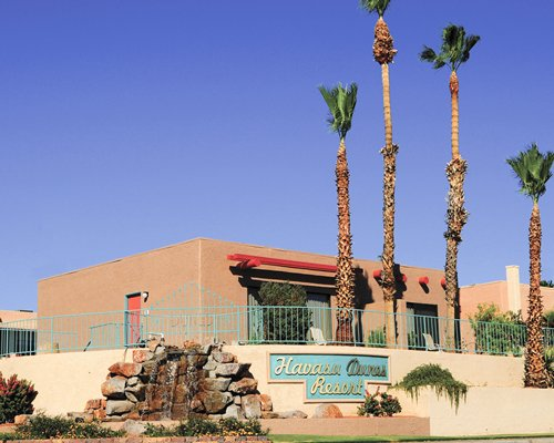 An exterior view of Havasu Dunes Resort with waterfalls and trees.