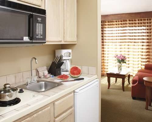 A well equipped kitchen alongside a living room.