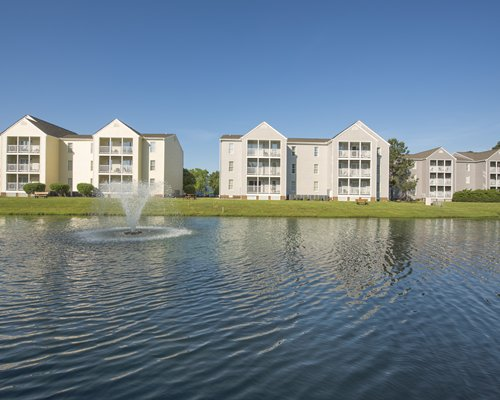 A waterfront with fountain alongside the multi story Wyndham Kingsgate resort.