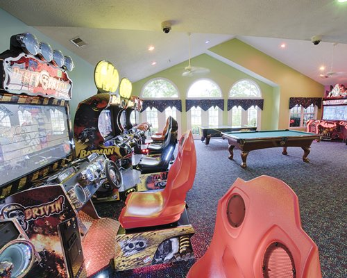 A recreational room with pool table and arcade game.