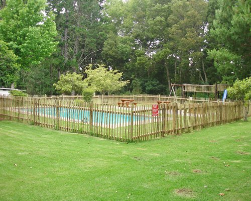 An outdoor swimming pool surrounded by lawns and trees.