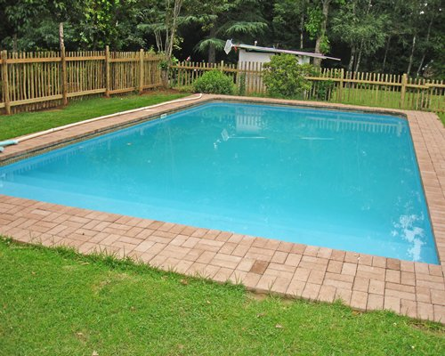 Outdoor swimming pool surrounded by wooded area.