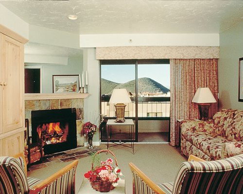 A well furnished living room with a fire in the fireplace and balcony.