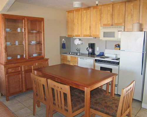 An open plan kitchen with wooden dining area.