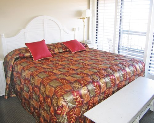 A well furnished bedroom with king bed and a balcony.