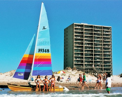 A group of people standing near a sail boat alongside a multi story resort condo.