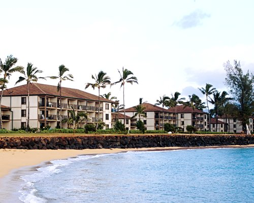 Scenic exterior view of multiple unit balconies at Pono Kai Resort alongside the beach.
