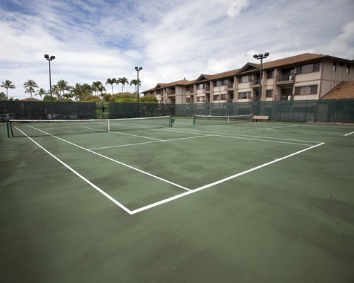 View of two outdoor tennis court alongside multi story resort units.