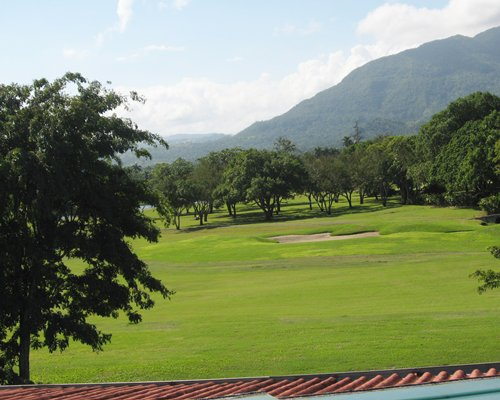 Golf course at Tropicana Caribe surrounded by wooded area.