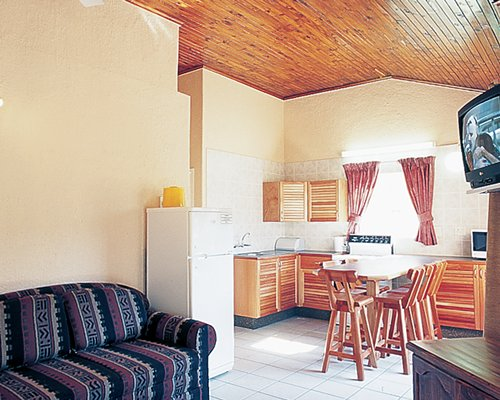 An open plan living dining and a kitchen area with a television.