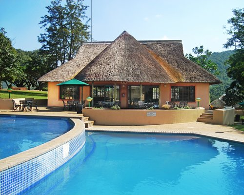 An outdoor swimming pool alongside a dining area.