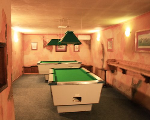 An indoor recreational room with two pool tables.