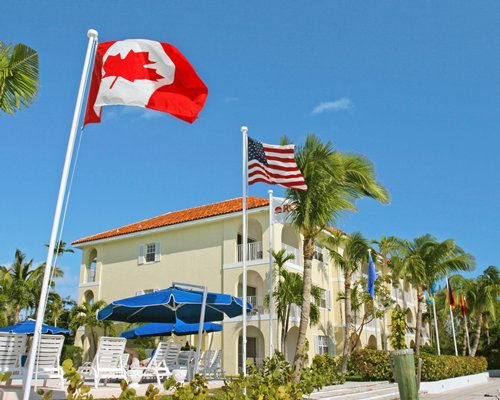An exterior view of the Paradise Harbour Club & Marina resort with American and Canadian flags.