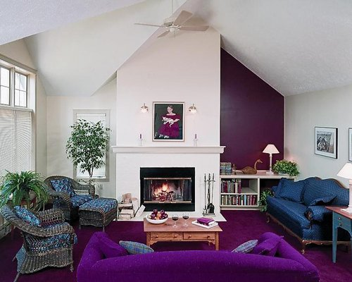A well furnished living room with double pull out sofas and fire at the fireplace.