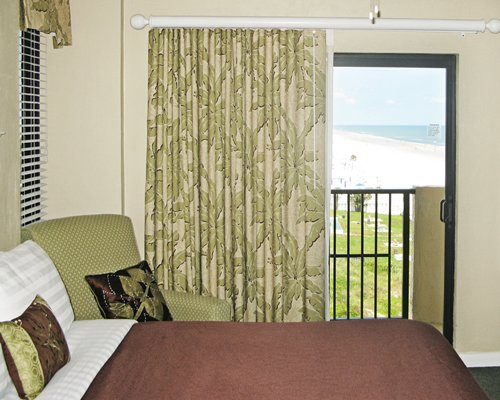 A well furnished bedroom with a balcony and beach view.