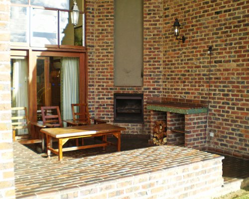 An exterior view of patio furniture and fireplace.