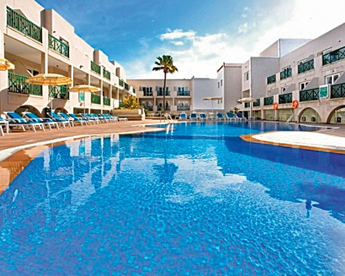 A large outdoor swimming pool with chaise lounge chairs and sunshades alongside the resort.