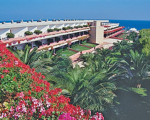 An exterior view of the Hotel Villaggio Cala Corvino resort property with trees and flowering shrubs.