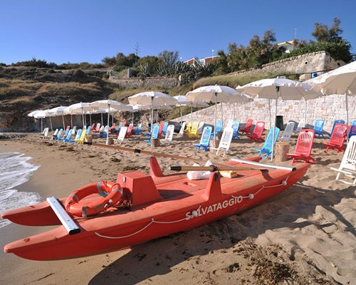 A beach view of chaise lounge chairs sunshades and boats.