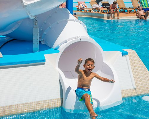 A kid sliding in a water slider.