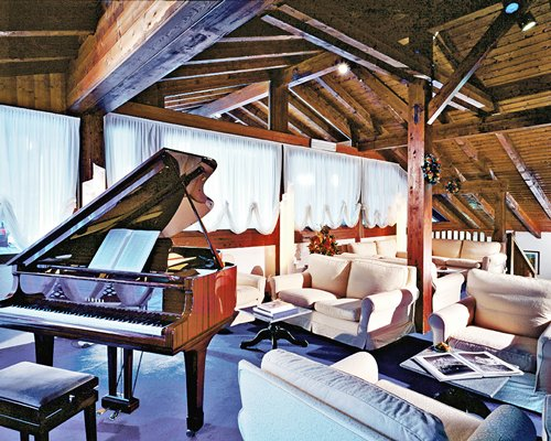 A well furnished lounge area alongside a piano.